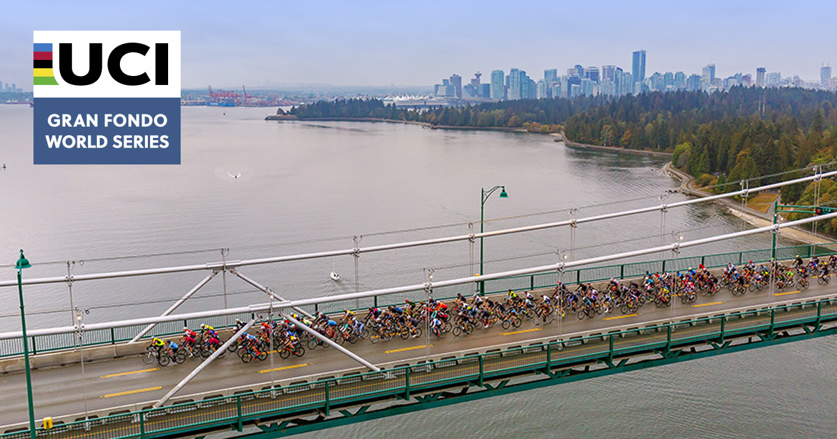 A large group of cyclists cross the Lions Gate bridge with Vancouver and Stanley Park in the background with UCI Gran Fondo World Series logo